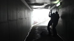 Man attacks a woman in a dark tunnel Stock Footage