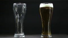Beer poured in empty glass on black background Stock Footage
