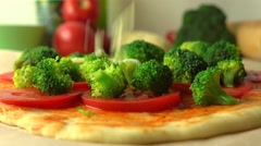 Pouring grated cheese over broccoli. Cooking homemade pizza, part of the set. 4K Stock Footage