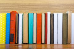 Books on grunge wooden table desk shelf in library. Back to school background Stock Photos