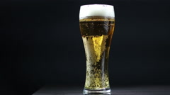 Bright Beer Bubbles. Full mug amber beer on a black background Stock Footage