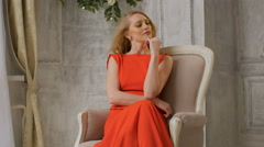 Pretty woman with blonde hair, dressed in red dress, sitting on armchair Stock Footage