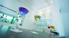 4K Cocktail glasses filled with colorful drinks on counter top in modern bar Stock Footage