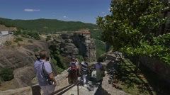Visitors walking down the stairways and taking photos of the Meteora landscape Stock Footage