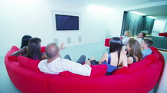 4K Friends watching TV together in luxurious home cinema viewing area Stock Footage
