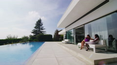 4K Exterior of luxury modern home with swimming pool & 2 young women relaxing Stock Footage