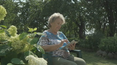 Aged woman 80s holding a digital tablet outdoors Stock Footage