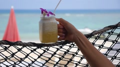 Female Hand with Fresh Pineapple Juice in Hammock on Beach. Stock Footage
