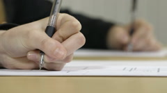 Close up of hands writing essays in an exam Stock Footage