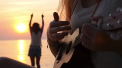 Hippie Girls Playing Ukulele Guitar and Dancing at Sunset Stock Footage