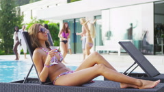 4K Summer pool party at luxury home, beautiful woman relaxing with a cocktail Stock Footage