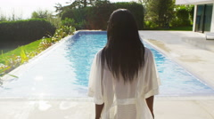 4K Beautiful woman outside modern home slips out of robe for a swim in the pool Stock Footage