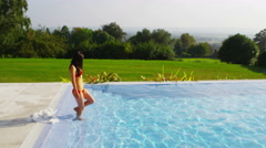 4K Beautiful woman outside modern home steps down into pool for a swim Stock Footage