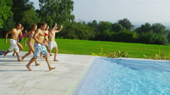 4K Happy friends at summer pool party, running jumping diving into water. Stock Footage