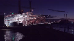 Beautiful shot of a large Mississippi paddlewheel riverboat docked at night near Stock Footage