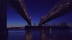 Beautiful shot of a massive cargo ship traveling under the Crescent City Bridge Stock Footage