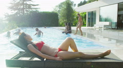 4K Beautiful woman relaxing by the pool in bikini, her friends play in the water Stock Footage