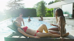 4K Beautiful women relaxing by the pool at summer party Stock Footage