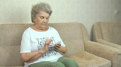 Old granny holding a mobile phone at home Stock Footage