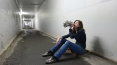 Drunk woman drinks alcohol in a tunnel Stock Footage