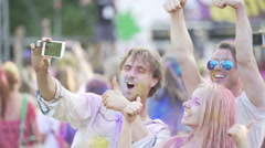 Excited friends covered in colorful powder at paint festival, posing for selfie Stock Footage