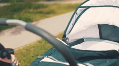 Mother sway baby carriage and speaking on phone in park. Summer day. Mothercare Stock Footage