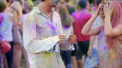 Excited young man and woman covered in Holi colors, dancing in crowd at concert Stock Footage