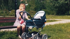Mother sway baby carriage and speaking on phone in summer park. Sunny day - stock footage