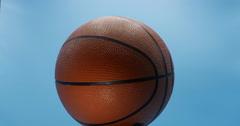 Basketball Turning Slow  Isolated on Blue Background 10bit, 4K Stock Footage