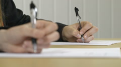 Hands writing in an exam with defocussed foreground Stock Footage