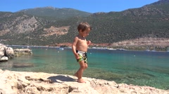 Happy child walks on cliffs against stunning sea view Stock Footage