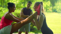 Fitness instructor helps to do stretching exercise. Multi ethnic friends Stock Footage
