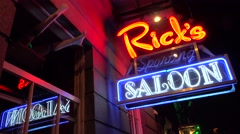 Neon sign for Rick's Saloon on Bourbon Street in New Orleans at night. Stock Footage
