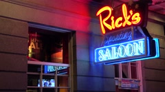 Neon sign for Rick's Saloon on Bourbon Street in New Orleans at night and legs Stock Footage