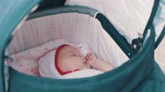 Little cute baby sleeping in baby carriage on street during walk. Summer day Stock Footage