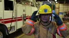 Asian fireman wiping sweat from his head and putting on helmet, portrait Stock Footage
