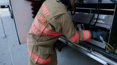 Fireman getting out the jaws of life from the fire engine Stock Footage