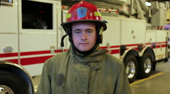 Young fireman putting on helmet and smiling, portrait Stock Footage
