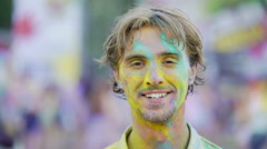 Cheerful young man covered in colorful dyes enjoying atmosphere at festival Stock Footage