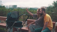 Mother and father with baby carriage on bench. Take selfie on smartphone. Family - stock footage