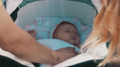 Young parents watching baby in carriage on bench. Family. Care. Happiness Stock Footage