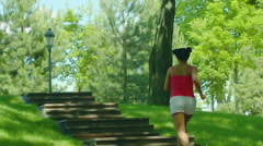 Woman run up stairs in slow motion. Girl running on stairway in park Stock Footage