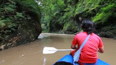 Tourist paddling on rubber boat at forest river in thailand Stock Footage