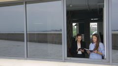 Women are discussing business issues in front of open window Stock Footage