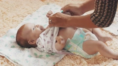 Mother undress smiling adorable baby on table. Communication. Motherhood. Love Stock Footage
