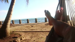Legs of person relaxing in a hammock by sea, afternoon Stock Footage
