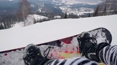 Two happy snowboarders sitting on the slope at a ski resort have a rest in Stock Footage