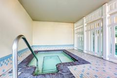 Interior of a swimming pool with Metal chrome plated ladder and tile flooring Stock Photos
