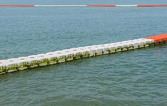 Buoy barrier on sea surface to protect people from boat Stock Photos