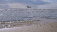 Girl and her father went into the sea on a background of storm clouds Stock Footage